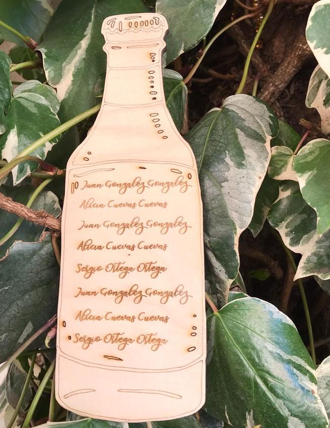 Botellas en madera natural con el nombre de los invitados grabados sobre la madera para distribuir mesas boda
